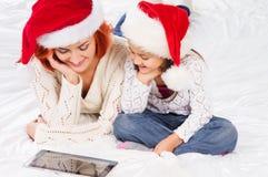 En lycklig moder och en dotter i julhattar Arkivfoto