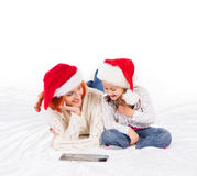 En lycklig moder och en dotter i julhattar royaltyfri bild