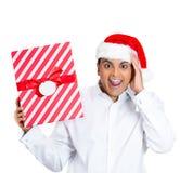 En lycklig och förvånad ung man i santas hatt Arkivfoto