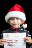 En lycklig pojke med en märka för santa Royaltyfri Bild