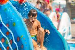 En lycklig pojke på vattenglidbana i en simbassäng som har gyckel under sommarsemester i en härlig aqua, parkerar en pojke arkivfoton