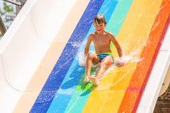 En lycklig pojke på vattenglidbana i en simbassäng som har gyckel under sommarsemester i en härlig aqua, parkerar en pojke arkivbild