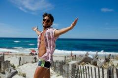 En lycklig sexig ung man som poserar med lyftta händer på stranden, bär i en swimwear, skjorta, på strandbakgrund fotografering för bildbyråer