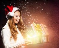 En lycklig tonårs- flicka som öppnar en julklapp Royaltyfria Foton