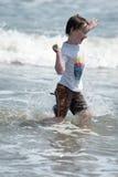 En lycklig ung pojkebarnspring som spelar och har gyckel i bränningen och vågorna av en sandig solig strand Arkivfoton