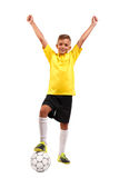 En lycklig unge med hans ben på en fotbollboll Ett gladlynt barn i en fotbolllikformig som isoleras på en vit bakgrund sportar Royaltyfria Bilder