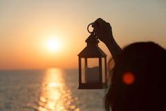 En lykta med en stearinljus i handen på gryning Arkivfoto