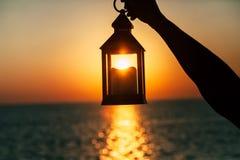 En lykta med en stearinljus i handen på gryning Arkivfoton