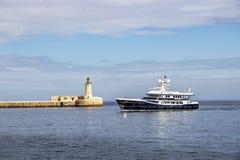 En lyxig yacht förbigår St Elmo Breakwater Head Light, Valletta, Malta royaltyfri fotografi