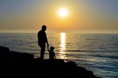 En människa rymmer ett barn vid handen, och de observerar solnedgången tillsammans royaltyfria foton