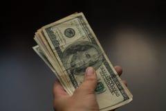 En mänsklig hand donerar 100 dollar royaltyfria bilder