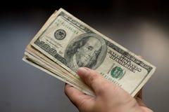 En mänsklig hand donerar 100 dollar arkivfoto