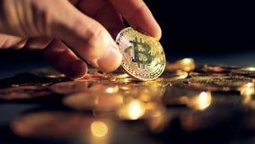 En mänsklig hand visar en av många guld- bitcoins arkivfilmer