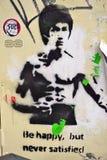 En målning för gatakonstgrafitti som föreställer den krigs- konstnären Bruce Lee i London Arkivbild