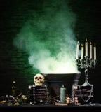 En mörk bakgrund med stearinljus och en skalle Arkivfoto