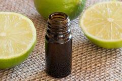 En mörk flaska av nödvändig olja för limefrukt med nya limefrukter royaltyfri foto