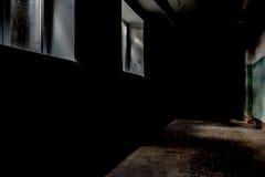 En mörk korridor med två rektangulära fönster, dunkelt dagsljus exponerar en del av väggen och golvyttersidan med en tegelplatta arkivfoto