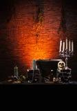 En mörkerbakgrund med stearinljus och en skalle Arkivbilder