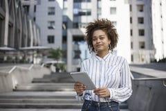 En mörkhyad flicka står på gatan nära affärsmitten Hon rymmer minnestavlan och leendena lägenheter som bygger arbete för ställe f arkivbild