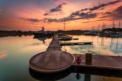 En majestätisk soluppgång med fartyget som vilar nära skeppsdockan som foregrou Arkivbilder