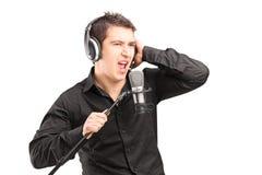 En male sångare med hörlurar som utför en song Arkivbild