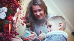 En mamma hjälper en son som dekorerar en julgran stock video