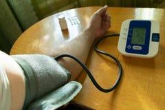 En man ändrar hans tryck av en tonometer som sitter på en tabell med en manschett på hans arm och en medicin i minnestavlor arkivfoton