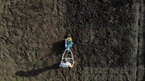 En man är en bonde i ett förorts- område, en grönsakträdgård, ploger landet med en odlare, en manuell motorisk plog lager videofilmer
