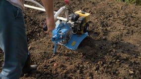 En man är en bonde i ett förorts- område, en grönsakträdgård, ploger landet med en odlare, en manuell motorisk plog stock video