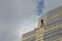 En man är den höga väggen för riskabel målning Royaltyfria Bilder