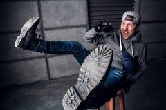 En man är en fotograf med kameran rolig framsida Mörkt - grå bakgrund placera text Fotografen skjuter på royaltyfri fotografi