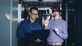 En man är inflyttningvirtuell verklighetexponeringsglas under vägledning av hans kollega arkivfilmer