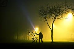 En man är stå, och rymma cykeln i dimmigt och mystiskt parkera royaltyfri fotografi