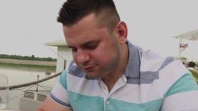 En man äter ivrigt skräpmat i en restaurang lager videofilmer