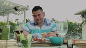 En man äter ivrigt skräpmat i en restaurang stock video