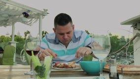 En man äter ivrigt skräpmat i en restaurang arkivfilmer