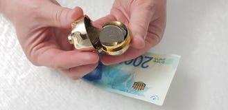En man öppnar den lilla guld- spargrisen som är full med fem sheckelmynt arkivfoton
