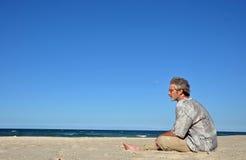 En man alone på den vita sandiga stranden arkivbild