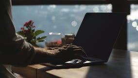 En man använder en bärbar dator i ett kafé på stranden stock video