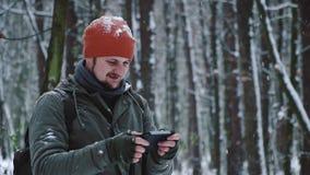 En man anv?nder en mobiltelefon i sociala n?tverk f?r en sn?ig skog, h?llande ?gonen p? video och att g?ra vad, skratta och jubla arkivfilmer
