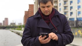 En man använder en mobiltelefon mot bakgrunden av en cityscape stock video