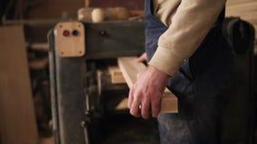 En man arbetar i ett snickeri shoppar Han går till den malande maskinen och installerar en lång stång in i den tillbaka sikt stock video