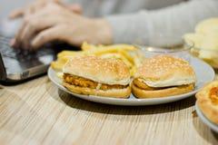 En man arbetar på en dator och äter snabbmat sjuklig mat: Bu Fotografering för Bildbyråer