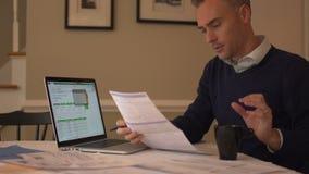 en man arbetar på hans räkningar med ett leende stock video