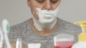 En man av en badrumspegel rakar framme hans framsida som täckas med vitt skum arkivfilmer