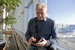 En man av pensionsåldern på flygplatsen arkivbild