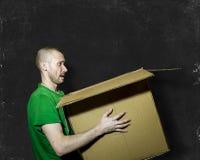 En man bär en ask på bakgrundsbrädet Arkivfoto