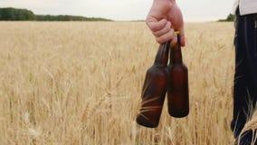 En man bär två flaskor av kallt öl över ett fält av korn Begreppet är att släcka din törstade ultrarapidvideo stock video