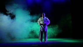 En man binder upp ett svart karatebälte mot en bakgrund av kulör rök stock video