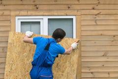 En man blockerar ett fönster med ett stort stycke av kryssfaner för en naturkatastrof, en orkan royaltyfria foton